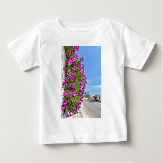 Hanging pink spanish daisies on wall near street baby T-Shirt