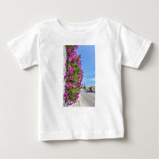 Hanging pink spanish daisies on wall near street baby T-Shirt