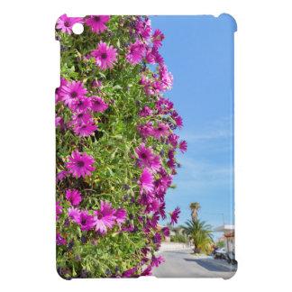Hanging pink spanish daisies on wall near street iPad mini covers