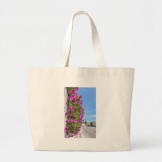 Hanging pink spanish daisies on wall near street large tote bag