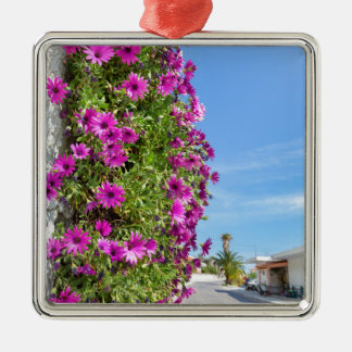 Hanging pink spanish daisies on wall near street metal ornament