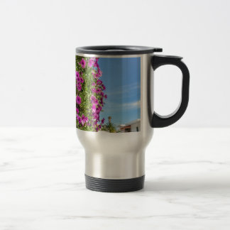 Hanging pink spanish daisies on wall near street travel mug