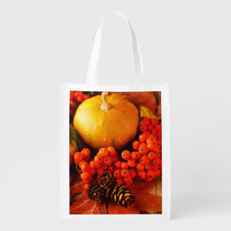 Harvested pumpkins with fall leaves grocery bags