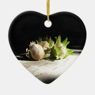 Hazelnuts on the table illuminated by the sunshine ceramic heart ornament