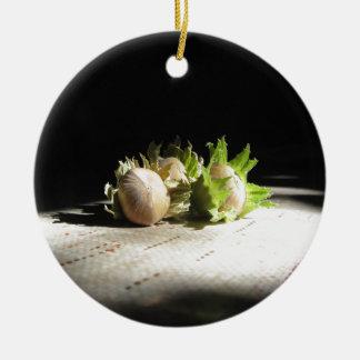 Hazelnuts on the table illuminated by the sunshine round ceramic ornament