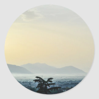 Hazy morning rooftops and a tall tree classic round sticker