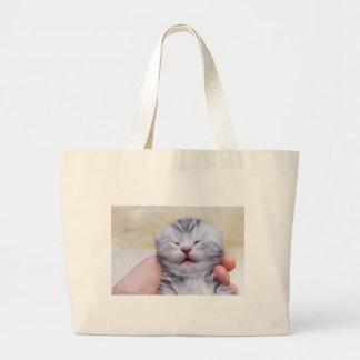 Head newborn silver tabby cat sleeping on hand large tote bag