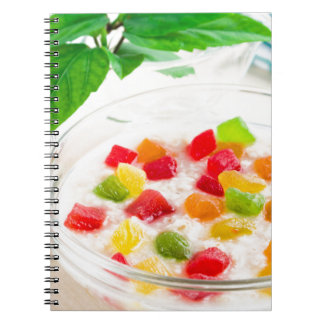 Healthy oatmeal close-up with candied fruit notebooks