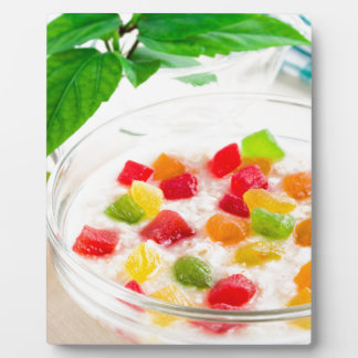 Healthy oatmeal close-up with candied fruit plaque