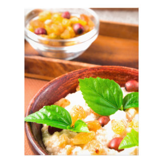 Healthy oatmeal with berries, raisins and herbs letterhead