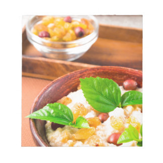 Healthy oatmeal with berries, raisins and herbs notepad