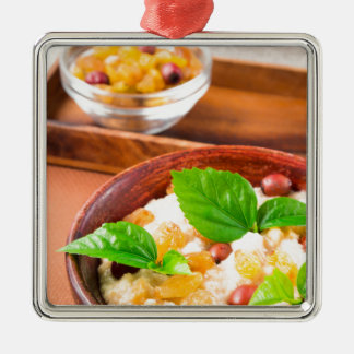 Healthy oatmeal with berries, raisins and herbs Silver-Colored square ornament
