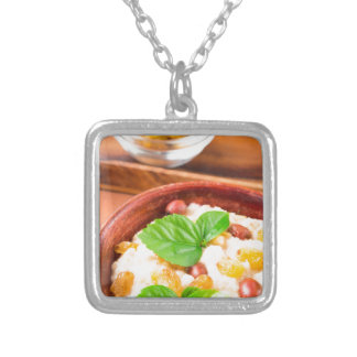 Healthy oatmeal with berries, raisins and herbs silver plated necklace