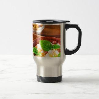 Healthy oatmeal with berries, raisins and herbs travel mug