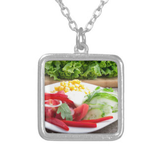 Healthy vegetarian dish on a gray textured fabric silver plated necklace