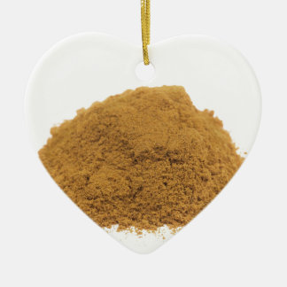 Heap of cinnamon powder on white background ceramic heart ornament