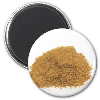 Heap of cinnamon powder on white background magnet