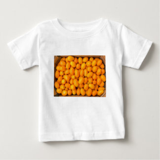 Heap of orange kumquats in cardboard box baby T-Shirt