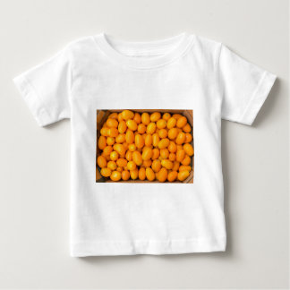 Heap of orange kumquats in cardboard box baby T-Shirt