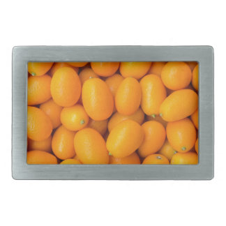Heap of orange kumquats in cardboard box belt buckles