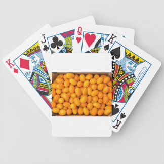 Heap of orange kumquats in cardboard box bicycle playing cards