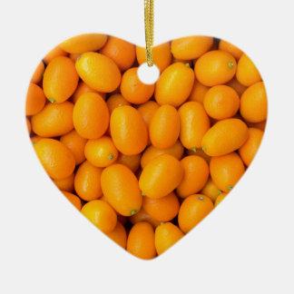 Heap of orange kumquats in cardboard box ceramic heart ornament