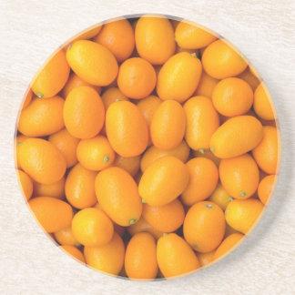 Heap of orange kumquats in cardboard box coaster