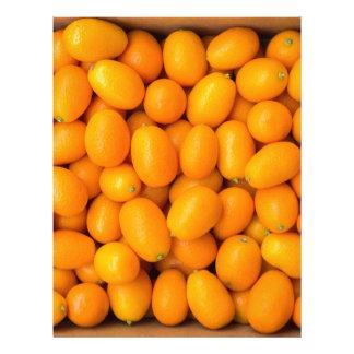 Heap of orange kumquats in cardboard box letterhead