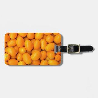 Heap of orange kumquats in cardboard box luggage tag