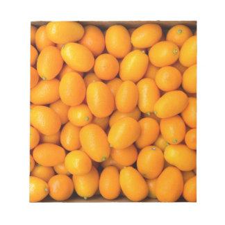 Heap of orange kumquats in cardboard box notepad