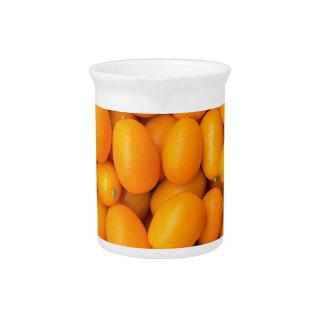 Heap of orange kumquats in cardboard box pitcher