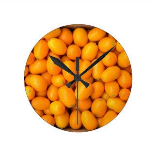 Heap of orange kumquats in cardboard box round clock