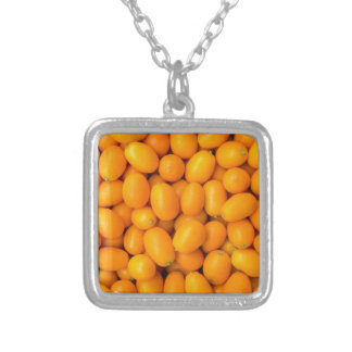 Heap of orange kumquats in cardboard box silver plated necklace