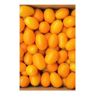 Heap of orange kumquats in cardboard box stationery