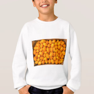 Heap of orange kumquats in cardboard box sweatshirt