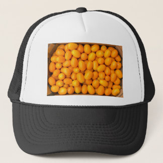 Heap of orange kumquats in cardboard box trucker hat