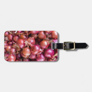 Heap of red onions on market bag tag