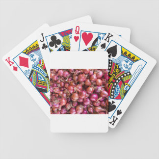 Heap of red onions on market bicycle playing cards