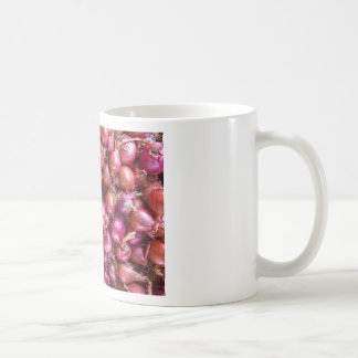 Heap of red onions on market coffee mug