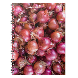 Heap of red onions on market notebook