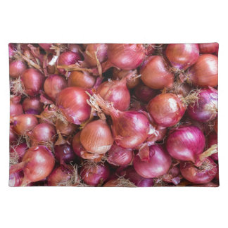 Heap of red onions on market placemat