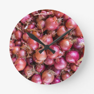 Heap of red onions on market round clock