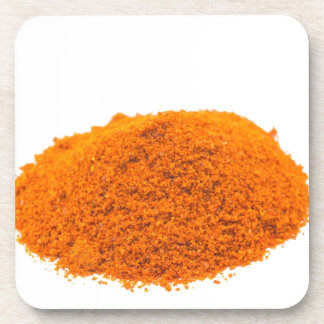 Heap of spice cayenne pepper powder on white coaster