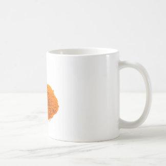Heap of spice cayenne pepper powder on white coffee mug