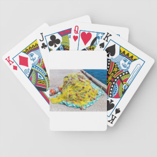 Heap of yellow fishnet on ground at sea bicycle playing cards
