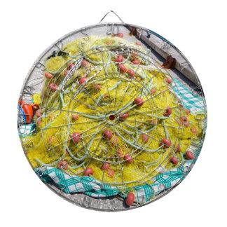 Heap of yellow fishnet on ground at sea dartboard