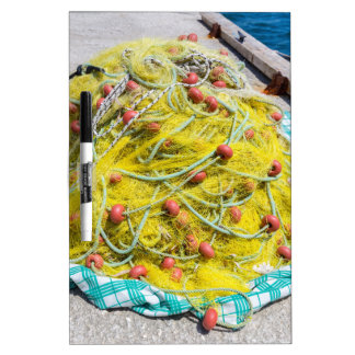 Heap of yellow fishnet on ground at sea dry erase board