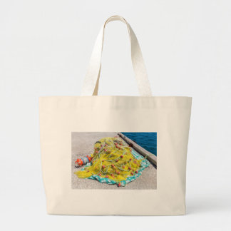 Heap of yellow fishnet on ground at sea large tote bag