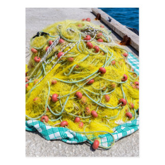 Heap of yellow fishnet on ground at sea postcard