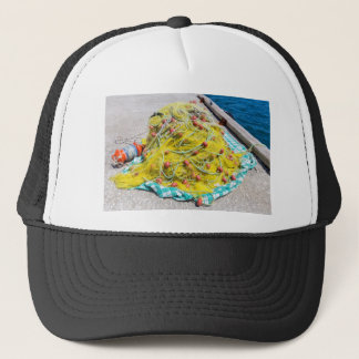 Heap of yellow fishnet on ground at sea trucker hat